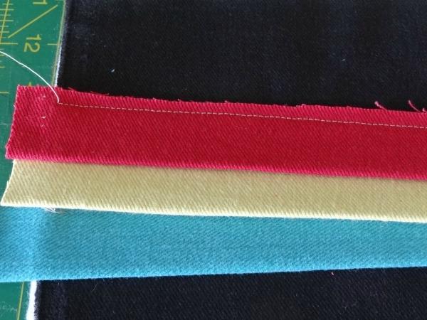 folded strips on denim clutch
