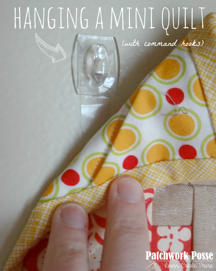 hanging a mini quilt with command hooks - learn how to use them. Super simple and all you need is safety pins and command hooks.